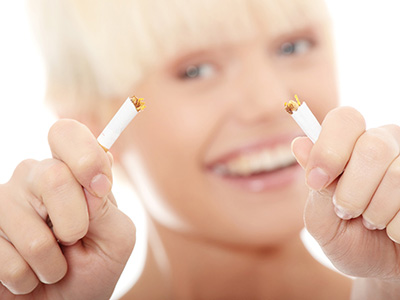 Young blond woman quiting smoking, isolated on white - focus on hand